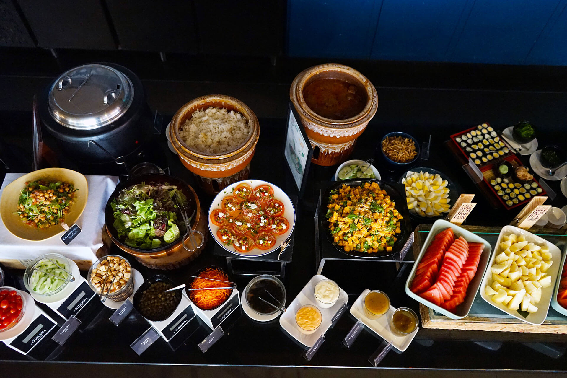 Breakfast buffet with savory & fruit options at KL Journal Hotel