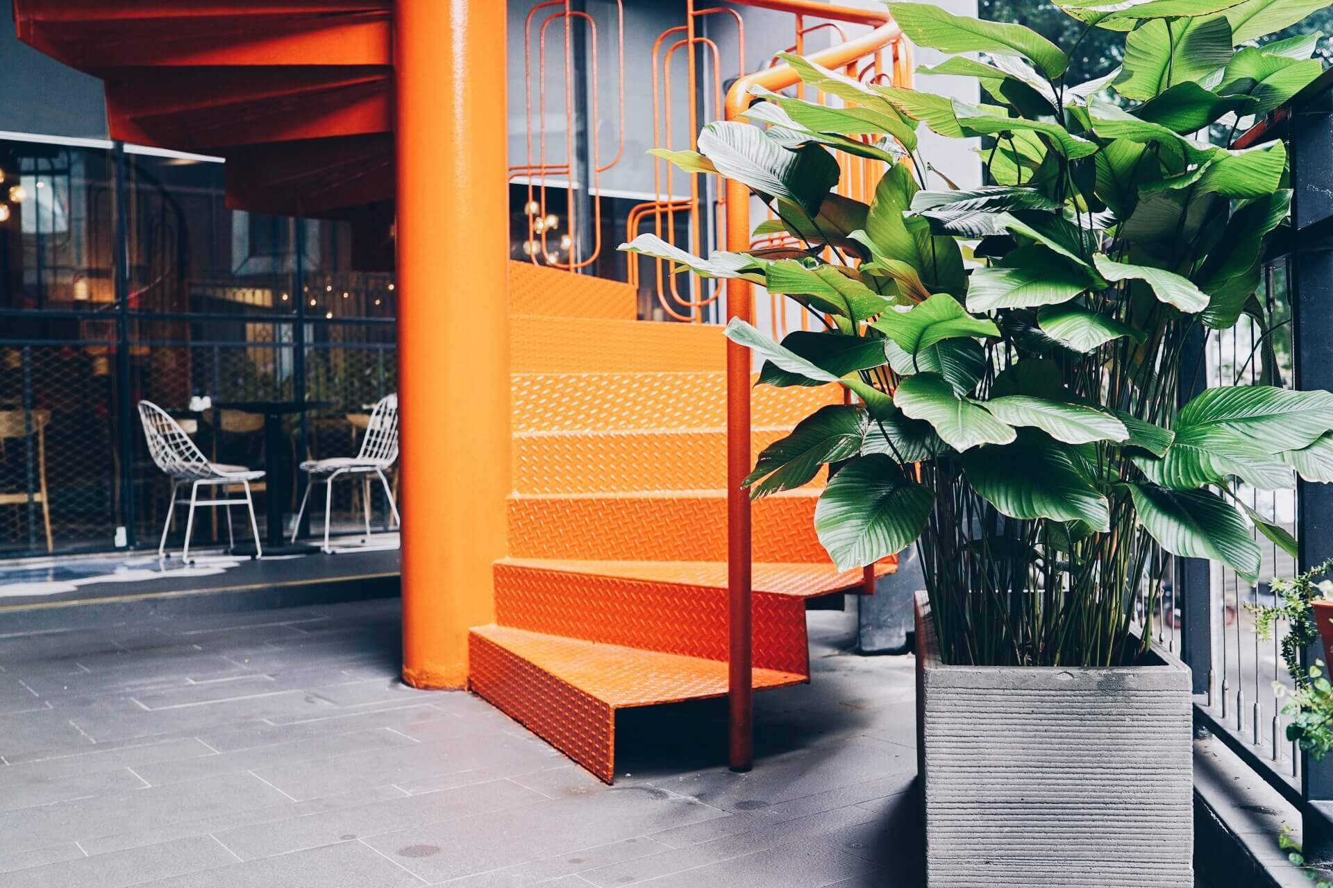 Potted plant next to a neon orange spiral staircase at the KL Journal Hotel