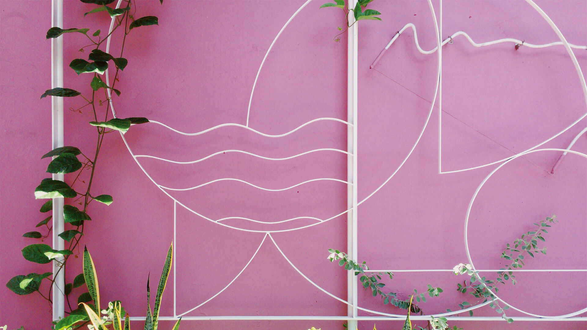 Abstract metal designs on a bright pink wall at KL Journal Hotel